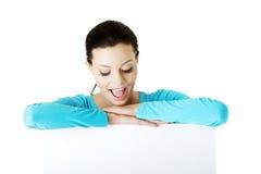 Junge glückliche Frau des Porträts mit leerem Brett Lizenzfreies Stockfoto