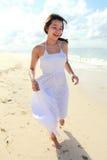 Junge glückliche Frau, die auf dem Strand läuft lizenzfreie stockfotografie
