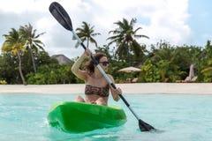 Junge glückliche Frau, die auf einer Tropeninsel in den Malediven Kayak fährt Freies blaues Wasser stockfoto