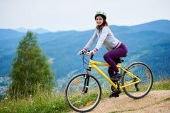 Junge glückliche Frau, die auf Mountainbike am Sommertag radfährt stockfotografie