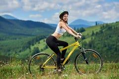 Junge glückliche Frau, die auf Mountainbike am Sommertag radfährt lizenzfreies stockfoto