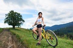 Junge glückliche Frau, die auf Mountainbike am Sommertag radfährt lizenzfreie stockfotos