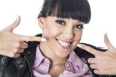 Junge glückliche Frau, die beide Finger auf ihr reizendes Lächeln zeigt Stockfotografie