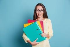 Junge glückliche Frau, die bunte Mappen über blauem Hintergrund hält Stockbild