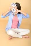 Junge glückliche Frau, die das Geld schaut gefallen und erfreut hält Stockbilder