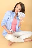 Junge glückliche Frau, die das Geld schaut gefallen und erfreut hält Stockbild