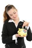 Junge glückliche Frau, die Geld in das piggybank einsetzt Lizenzfreies Stockfoto