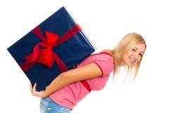 Junge glückliche Frau, die großes Geschenk trägt Lizenzfreie Stockfotografie