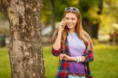 Junge glückliche Frau, die am Handy im Sommerstadtpark spricht Schönes modernes Mädchen in der Sonnenbrille mit einem Smartphone, Stockfotografie