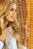 Junge glückliche Frau, die heraus das Fenster durch die Vorhänge schaut Stockfoto