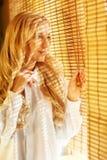Junge glückliche Frau, die heraus das Fenster durch die Vorhänge schaut Stockbild