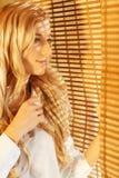 Junge glückliche Frau, die heraus das Fenster durch die Vorhänge schaut Lizenzfreies Stockbild
