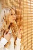 Junge glückliche Frau, die heraus das Fenster durch die Vorhänge schaut Lizenzfreies Stockfoto