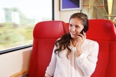 Junge glückliche Frau, die im Zug spricht am intelligenten Telefon sitzt lizenzfreie stockfotos