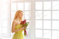 Junge glückliche Frau, die mit Tulpenbündel im gelben Kleid lächelt stockfoto