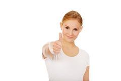 Junge glückliche Frau, die oben Daumen gestikuliert Lizenzfreie Stockfotografie