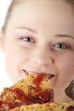 Junge glückliche Frau, die Pizza isst Lizenzfreie Stockfotos