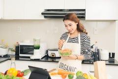 Junge glückliche Frau, die Salat isst Gesunder Lebensstil mit grünem foo Stockfotografie