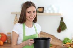 Junge glückliche Frau, die Suppe in der Küche kocht Gesunde Mahlzeit, Lebensstil und kulinarisches Konzept Lächelndes Kursteilneh lizenzfreies stockbild