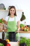 Junge glückliche Frau, die Suppe in der Küche kocht Gesunde Mahlzeit, Lebensstil und kulinarisches Konzept Lächelndes Kursteilneh lizenzfreie stockfotografie