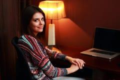 Junge glückliche Frau, die am Tisch sitzt Stockfotografie