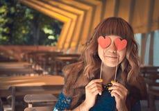 Junge glückliche Frau, die zwei Herzen hält stockfotografie