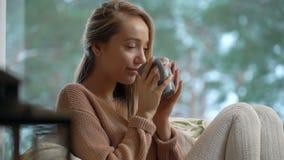 Junge glückliche Frau genießen von der Schale heißem Kaffee nach Hause sitzend durch das große Fenster mit Winterschnee-Baumhinte stock video footage