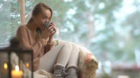 Junge glückliche Frau genießen von der Schale heißem Kaffee nach Hause sitzend durch das große Fenster mit Winterschnee-Baumhinte stock video