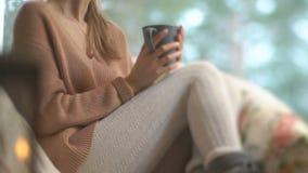 Junge glückliche Frau genießen von der Schale heißem Kaffee nach Hause sitzend durch das große Fenster mit Winterschnee-Baumhinte stock footage
