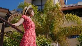 Junge glückliche Frau genießt die Sonnenstellung im Hotelgarten mit den Palmen, die rotes Kleid, Hut und Sonnenbrille tragen stock video