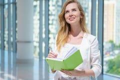 Junge glückliche Frau im Büro Lizenzfreie Stockfotos