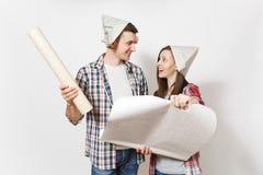 Junge glückliche Frau, Mann in der zufälligen Kleidung und Zeitungshüte, die Tapetenrollen halten Paare lokalisiert auf weißem Hi lizenzfreie stockfotografie