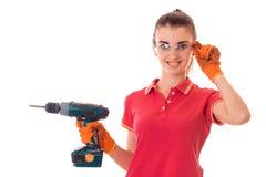 Junge glückliche Frau mit dem dunklen Haar im uniforl lässt Erneuerungen mit ihre Hände herein bohren, die auf weißem Hintergrund stockbilder