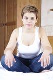 Junge glückliche Frau mit dem kurzen Haar, das auf Bett sitzt Lizenzfreie Stockfotos