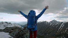 Junge glückliche Frau mit dem Rucksack, der auf einem Felsen mit den angehobenen Händen steht und zu einem Tal unten schaut stock video footage