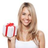 Junge glückliche Frau mit einem Geschenk Lizenzfreie Stockfotografie