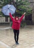Junge glückliche Frau mit einem Regenschirmtanzen im Regen Stockfoto