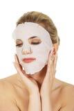 Junge glückliche Frau mit Gesichtsmaske stockbilder