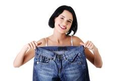 Junge glückliche Frau mit großen Hosen Lizenzfreie Stockbilder