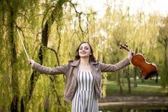 Junge glückliche Frau mit Violine und Bogen stockfotografie