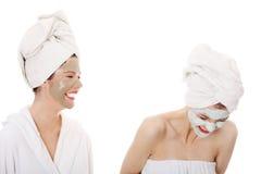 Junge glückliche Frauen mit Gesichtslehmschablone Stockbilder