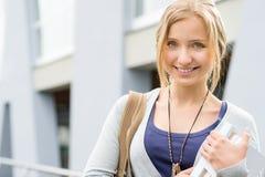 Junge glückliche Frauenholdingbücher zur Schule Stockbild