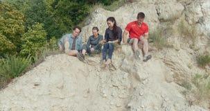 Junge glückliche Freunde, die auf dem Berg sitzen und Erholung in der Natur genießen stock video