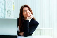 Junge glückliche Geschäftsfrau, die auf ihrem Arbeitsplatz sitzt und copyspace betrachtet Stockbilder
