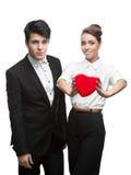 Junge glückliche Geschäftsleute, die roten Valentinsgruß anhalten Lizenzfreie Stockfotografie