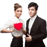 Junge glückliche Geschäftsleute, die roten Valentinsgruß halten Lizenzfreies Stockfoto