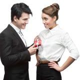 Junge glückliche Geschäftsleute, die rotes Geschenk halten Stockfoto