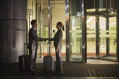 Junge glückliche Geschäftsleute Händeschütteln außerhalb des Büros nachts stockbilder