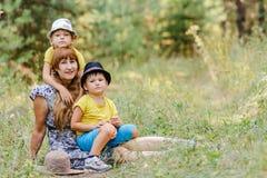 Junge glückliche Großmutter mit zwei kleinen Enkelkindern, die an sitzen lizenzfreie stockfotos