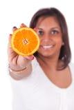 Junge glückliche indische Frau, die eine orange Scheibe anhält lizenzfreie stockfotografie